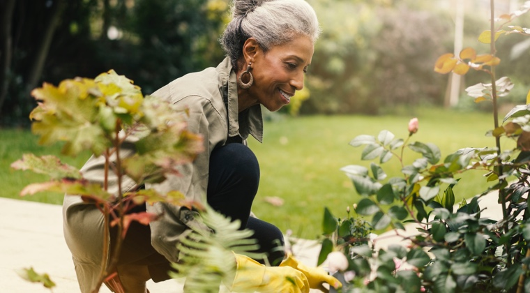 a woman smiling and working in her garden